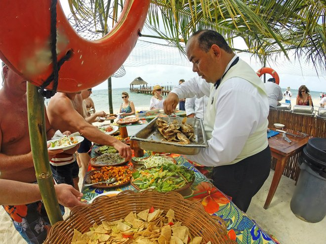Guests line up to sample fresh fish prepared right on the beach.